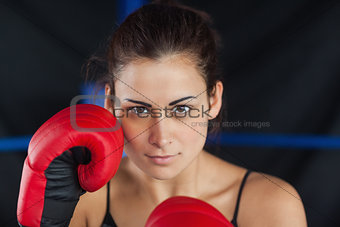 Close up portrait of a beautiful woman in red boxing gloves