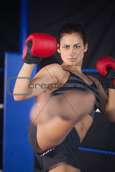 Pretty female boxer performing an air kick in the ring