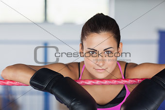 Beautiful young woman in black boxing gloves