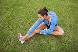 Sporty woman stretching her leg while sitting on the grass