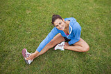 Pretty sporty woman stretching her leg while sitting on the grass