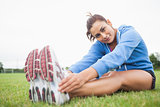 Pretty sporty woman stretching her legs while sitting on the grass