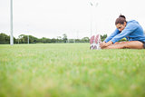 Sporty woman stretching her legs while sitting on grass