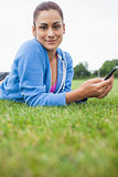 Pretty woman with mobile phone lying on grass