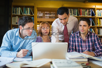 Mature students with teacher and laptop in library
