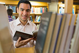 Smiling mature student with book by shelf in library