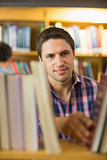 Mature student selecting book from shelf in the library