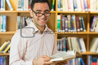 Smiling mature student reading book in library