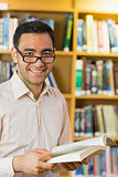 Smiling mature student with book in library