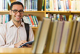 Smiling mature student using tablet PC in library