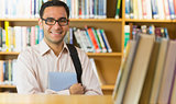 Smiling mature student with tablet PC in library