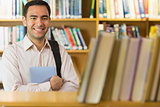 Smiling mature student with tablet PC in the library