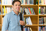 Smiling mature student with bag in library