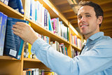 Mature student selecting book from shelf in library