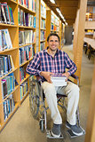 Man in wheelchair by bookshelf in library