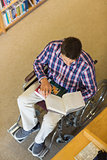 Man in wheelchair reading a book in library