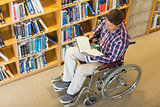 Man in wheelchair reading a book in the library