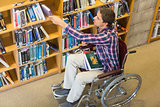 Man in wheelchair selecting book in the library