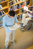 Man and disabled student in wheelchair reading books in library