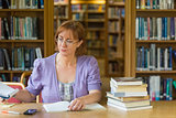 Mature female student studying at desk in the library