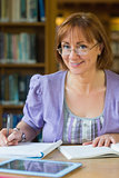 Smiling mature female student at desk in the library