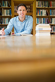Smiling mature student studying at library desk