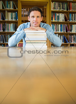Mature student with stack of books at desk in the library