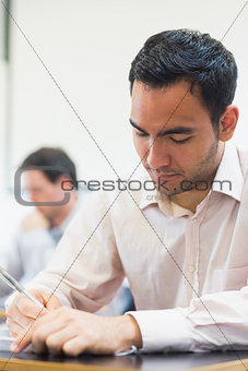 Mature student taking notes in classroom