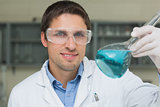 Male researcher  holding flask with blue liquid in the lab