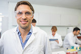 Smiling scientist with colleagues at work in the lab