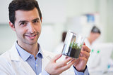 Smiling male researcher holding young plant at lab