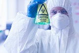 Scientist in protective suit with hazardous chemical in flask