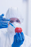 Researcher in protective suit injecting tomato at lab