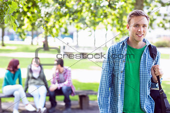 Portrait of college boy with blurred students in park
