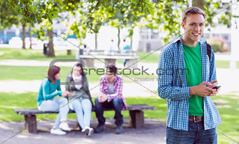College boy text messaging with blurred students in park