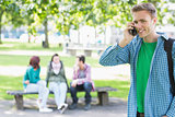 College boy using mobile phone with students in park