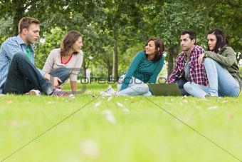 College students with laptop sitting in park