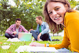 Female writing notes with students using laptop in park