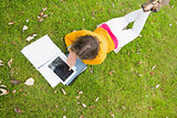 Female student using tablet PC in the lawn