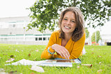 Smiling female student using tablet PC in lawn