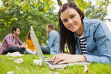 Smiling female using laptop with other students in park