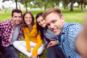 Portrait of cheerful college students in park