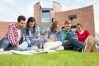 Students using tablet PCs in the lawn against college building