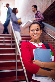 Smiling female holding books with students on stairs in college