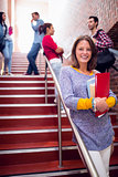 Female holding books with students on stairs in college