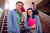 Couple with students behind on stairs in college