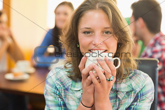 Close up of a smiling female having coffee at  coffee shop