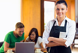 Waitress with two students using laptop at  coffee shop
