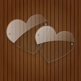 Vector two glass hearts over wooden background.
