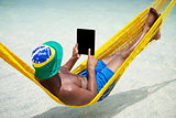 Brazilian Man Relaxes Using Tablet in Hammock on Beach
